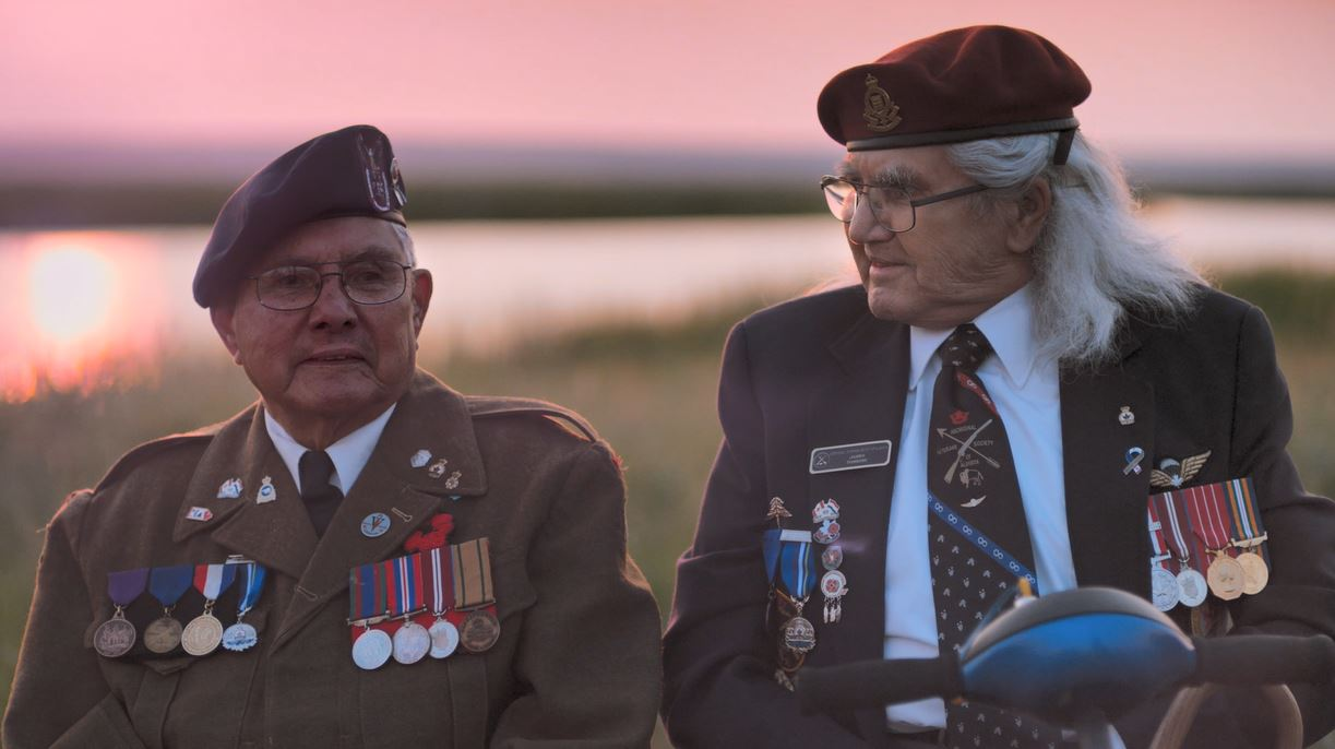 Two veterans sit beside each other in a still from Alex Lazarowich's film Cree Code Talker