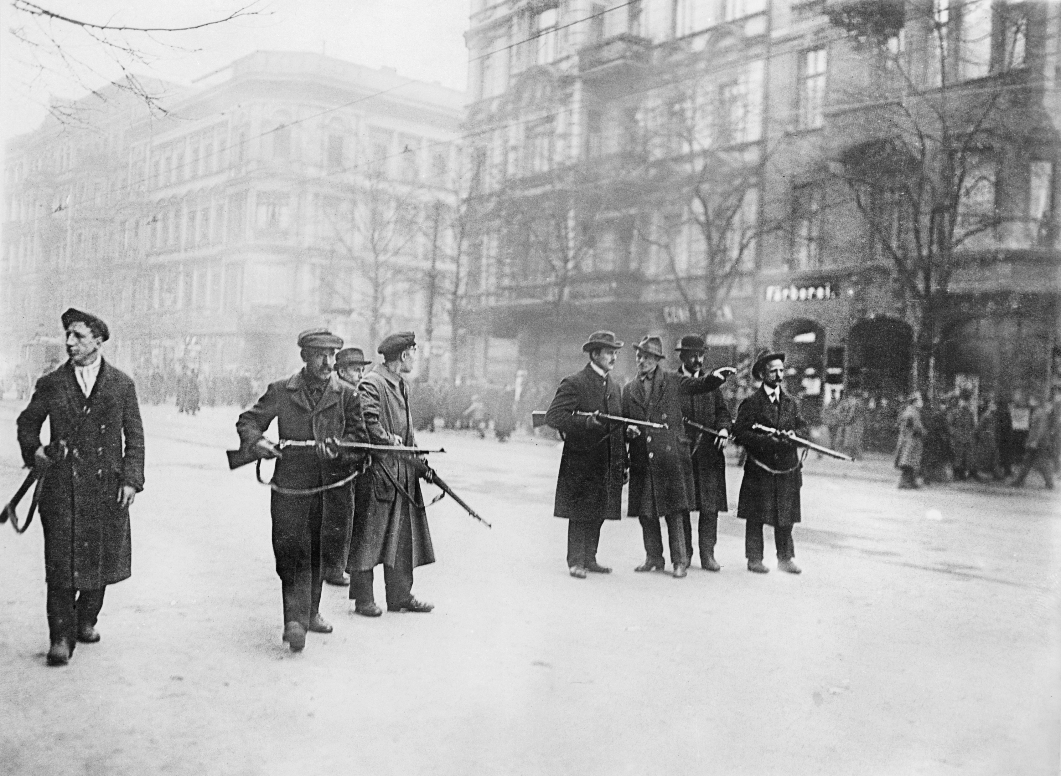 A line of armed revolutionaries of the Spartacist Movement standing in a Berlin street.