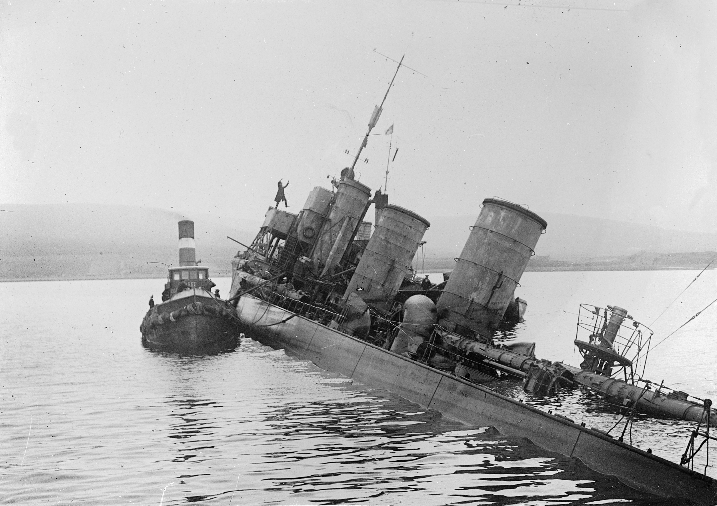 Tug alongside scuttled German destroyer G 102 at Scapa Flow