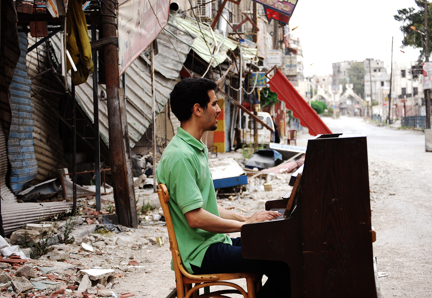 Aeham Ahmad sitting at a piano in a damaged street in Syria