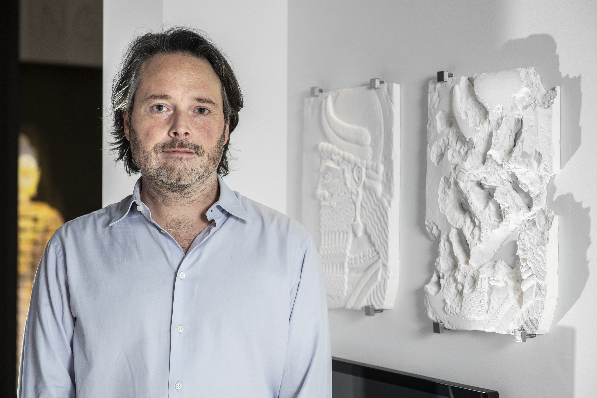 Portrait of artist Piers Secunda standing in front of one of his artworks in What Remains at IWM London