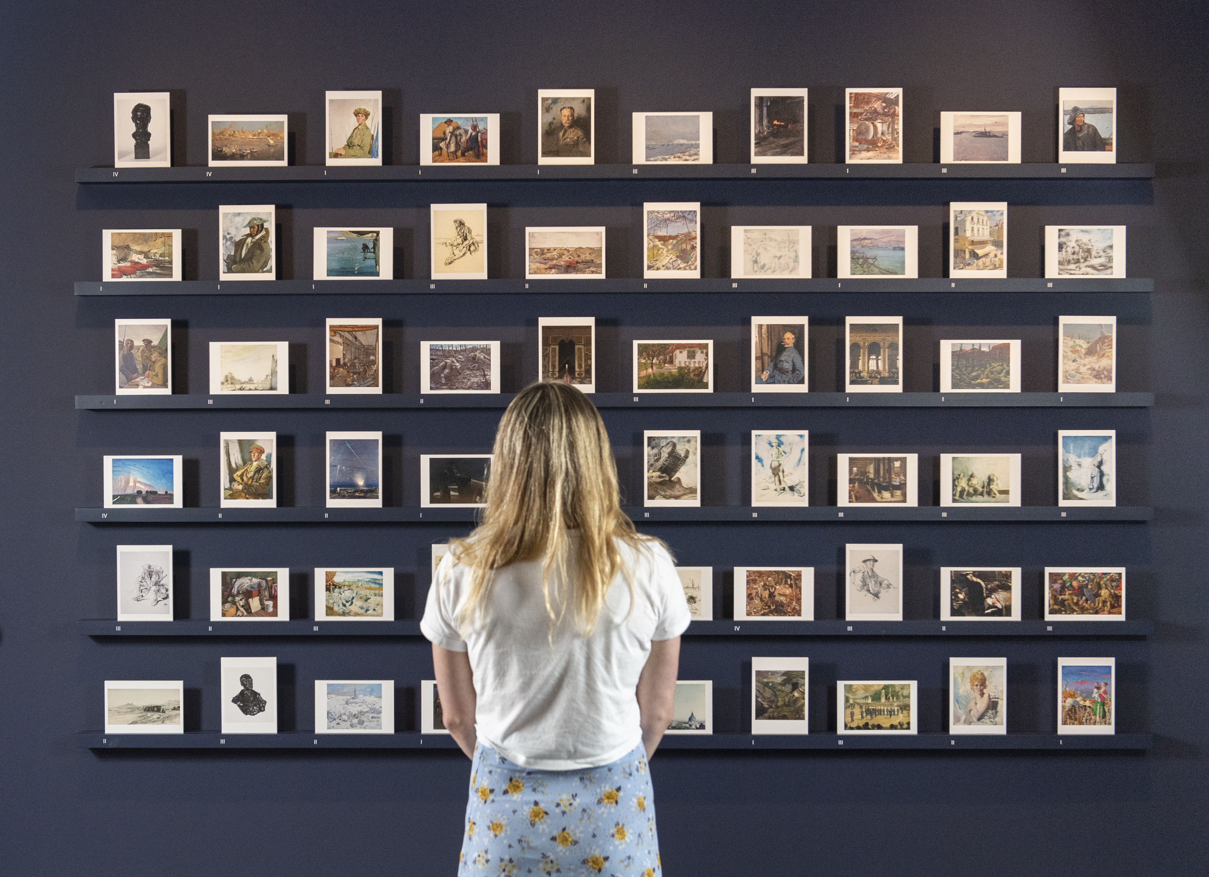 Woman looking at a wall of postcard-sized images in Art in Exile exhibition.