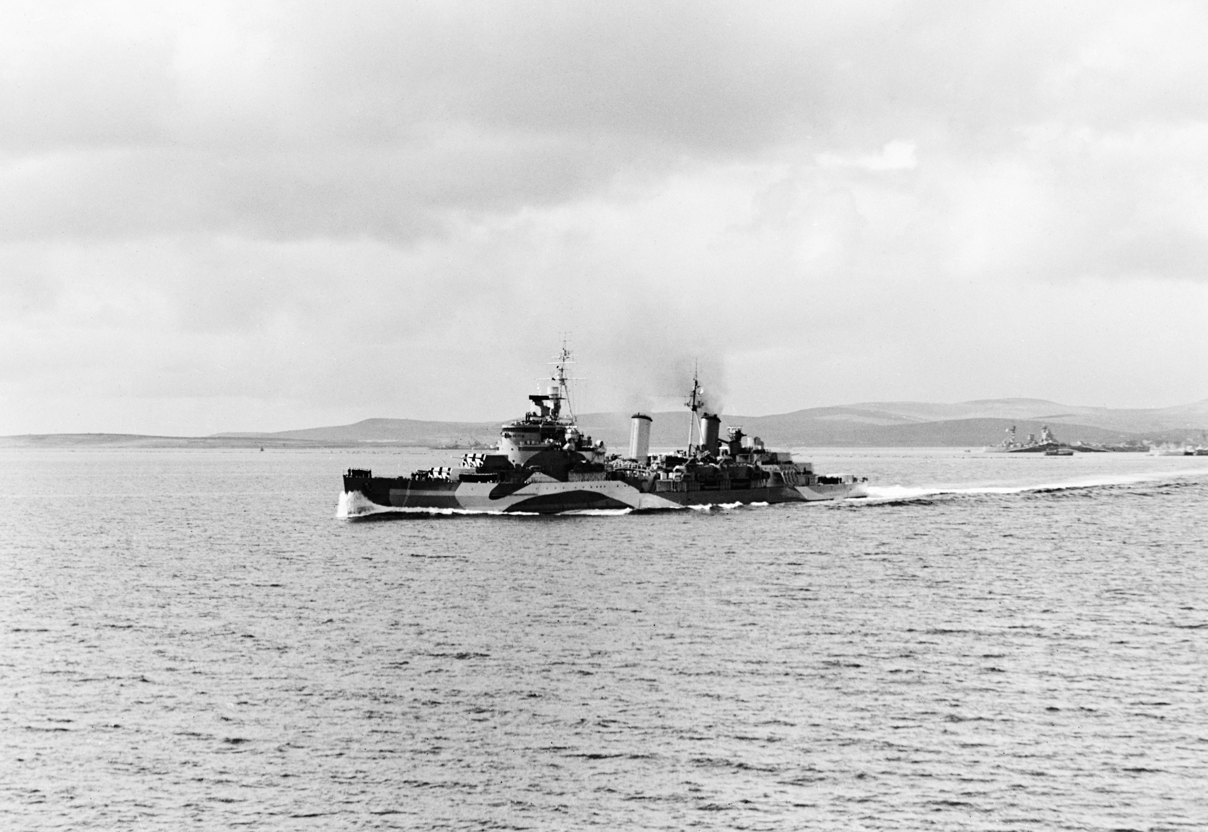 © IWM (A 25665) HMS Belfast leaving Scapa Flow for the Normandy beaches in June 1944. The cruiser is reported to have fired some of the first shots on D-Day.