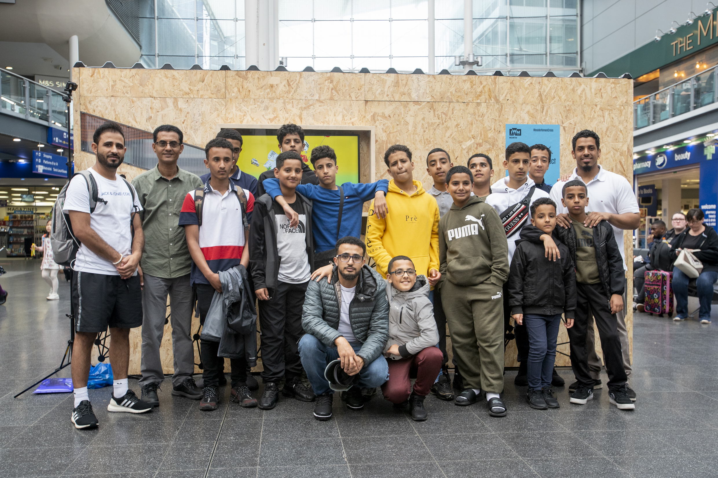 Group portrait photograph of young people performing a spoken word piece after participating in workshops with spoken word poet Amerah Saleh