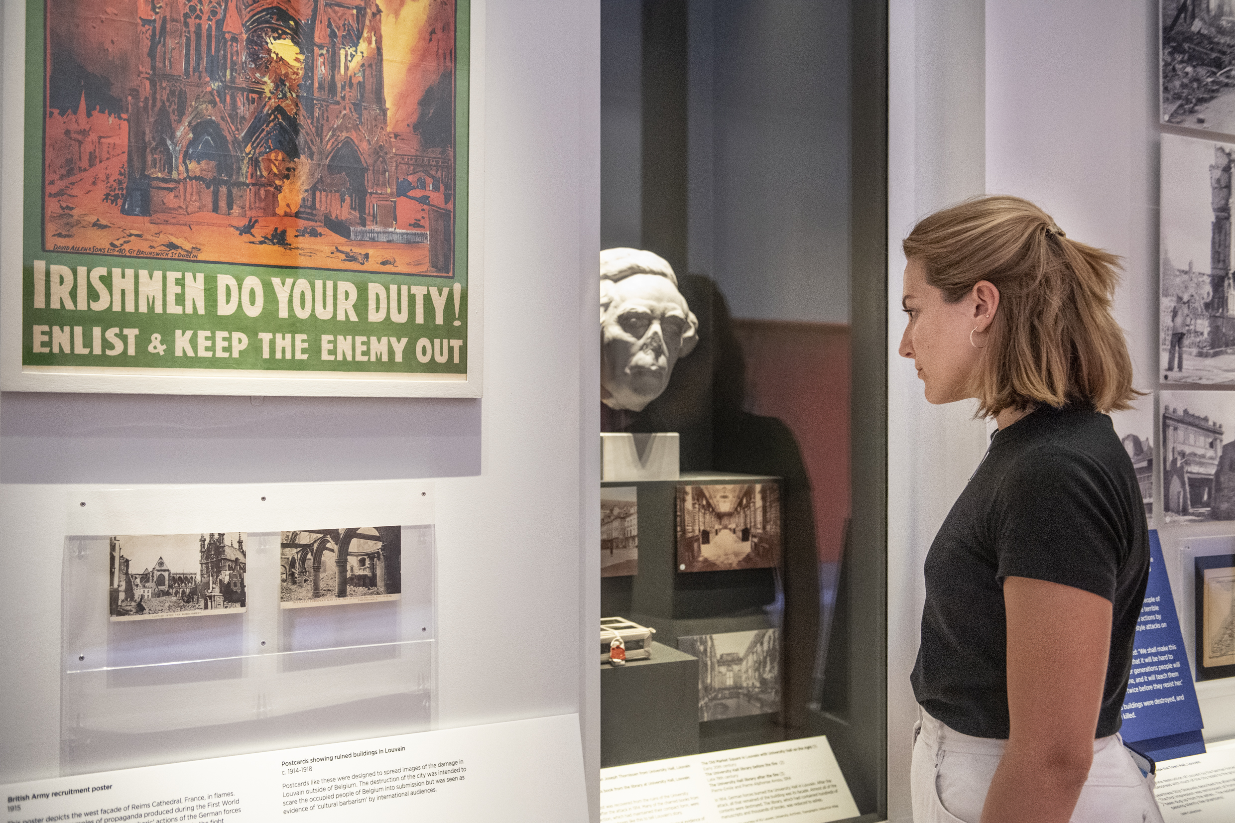 Woman looks at part of a statue and a poster in the What Remains exhibition