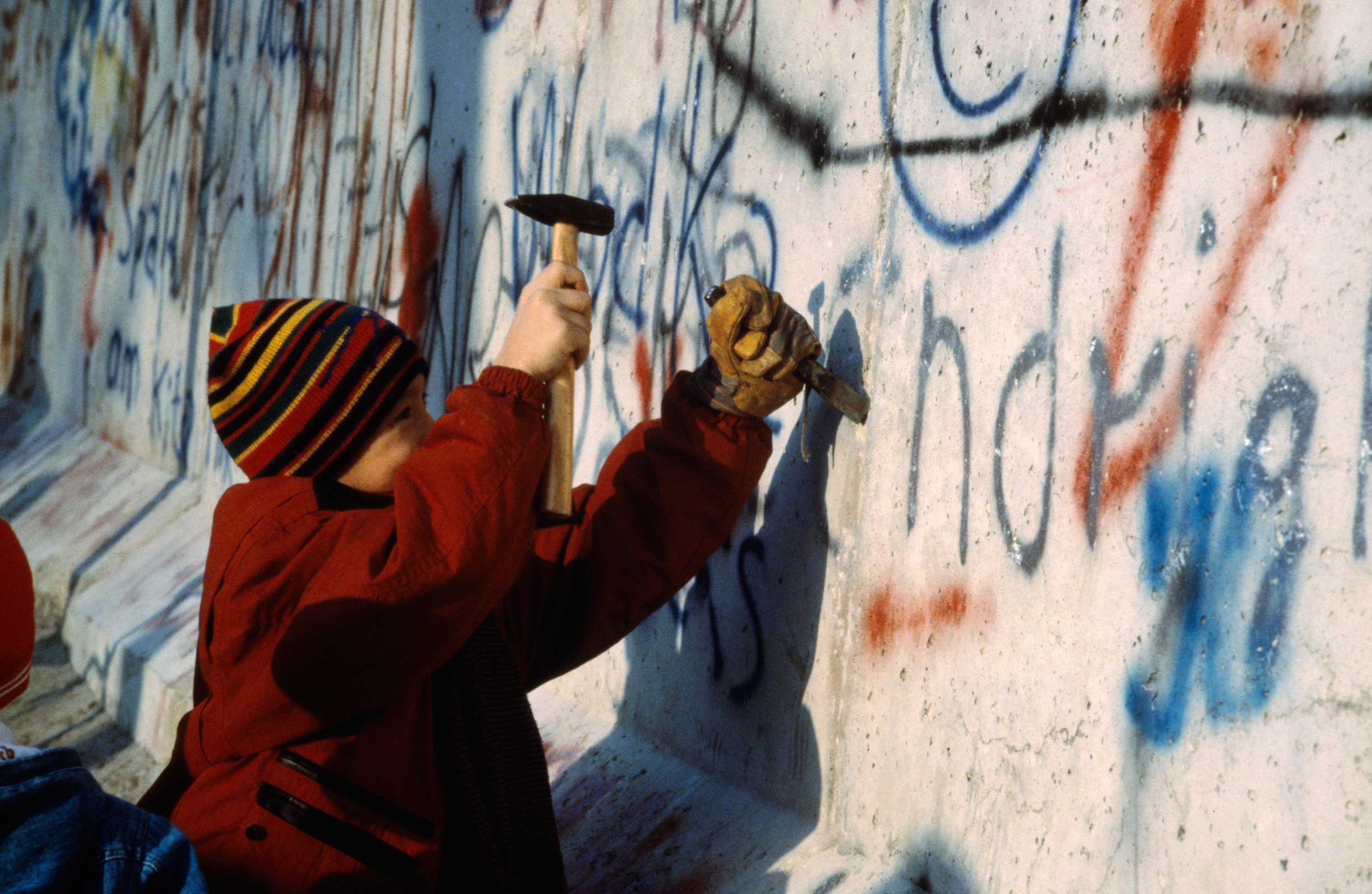 A child using a hammer and chisel to remove a piece of the Berlin Wall after its opening by the East German Government on 9 November 1989