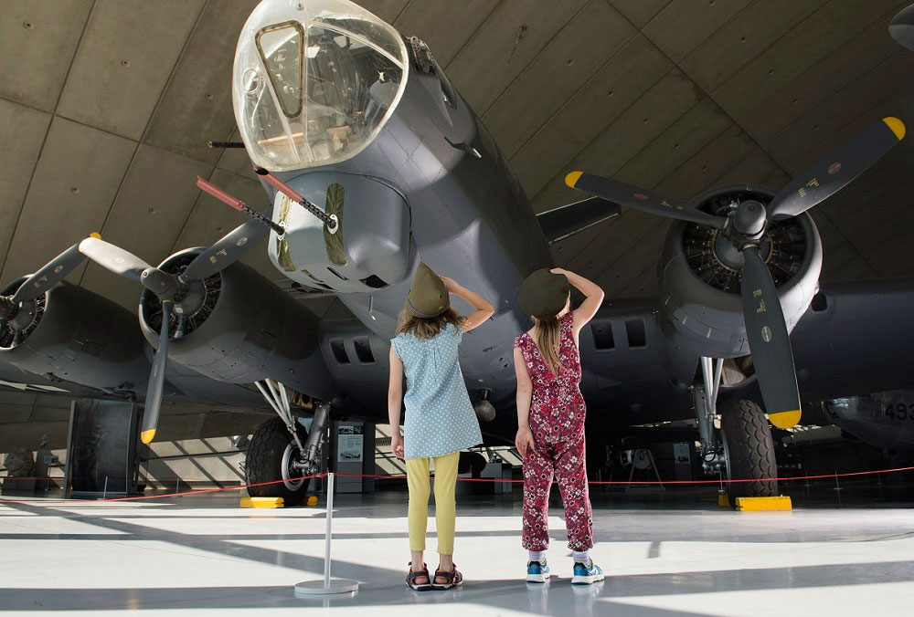 Girls saluting in front of B-17 inside the American Air Museum