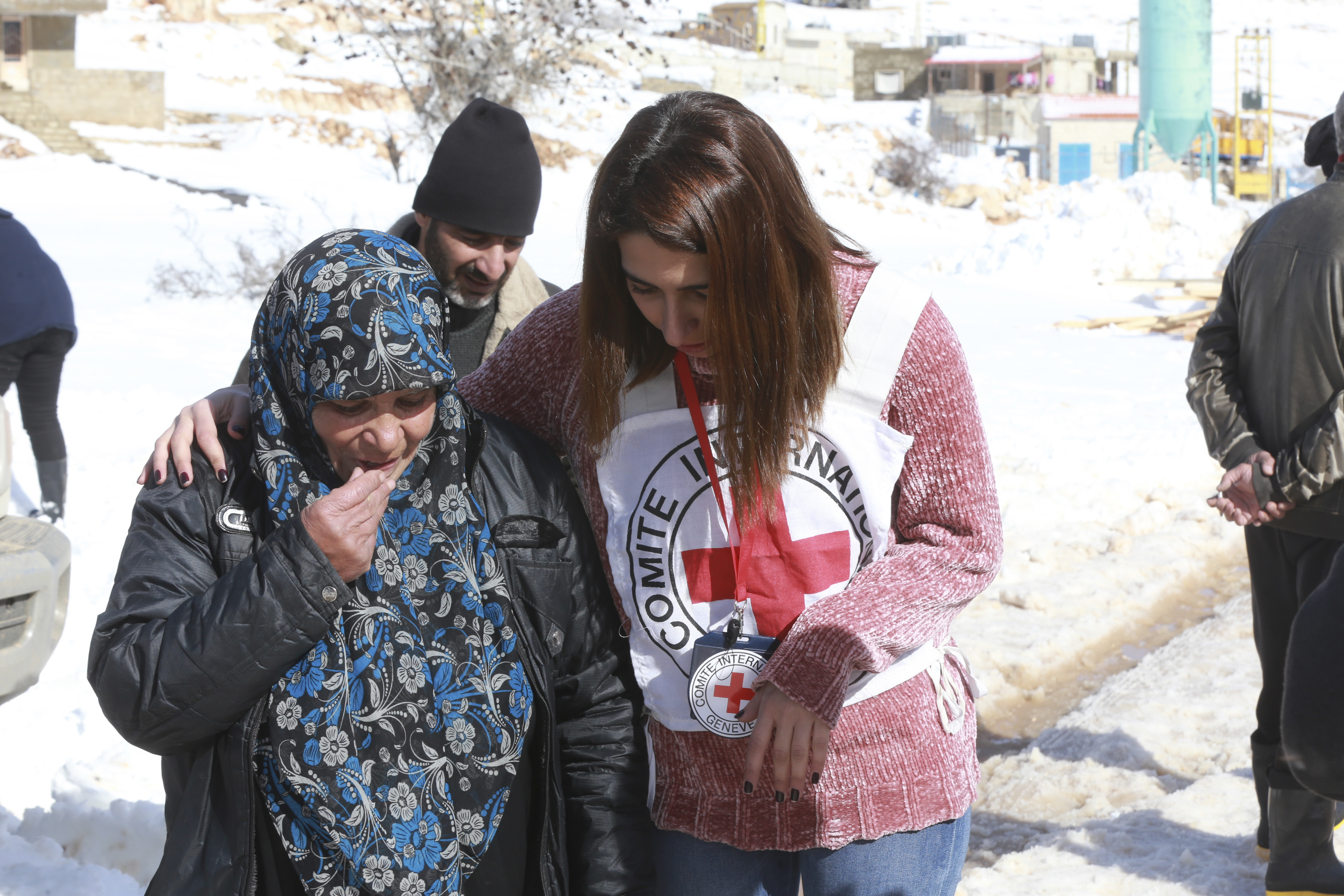 An aid worker in Arsal refugee camp in Lebanon with her arm around a woman.