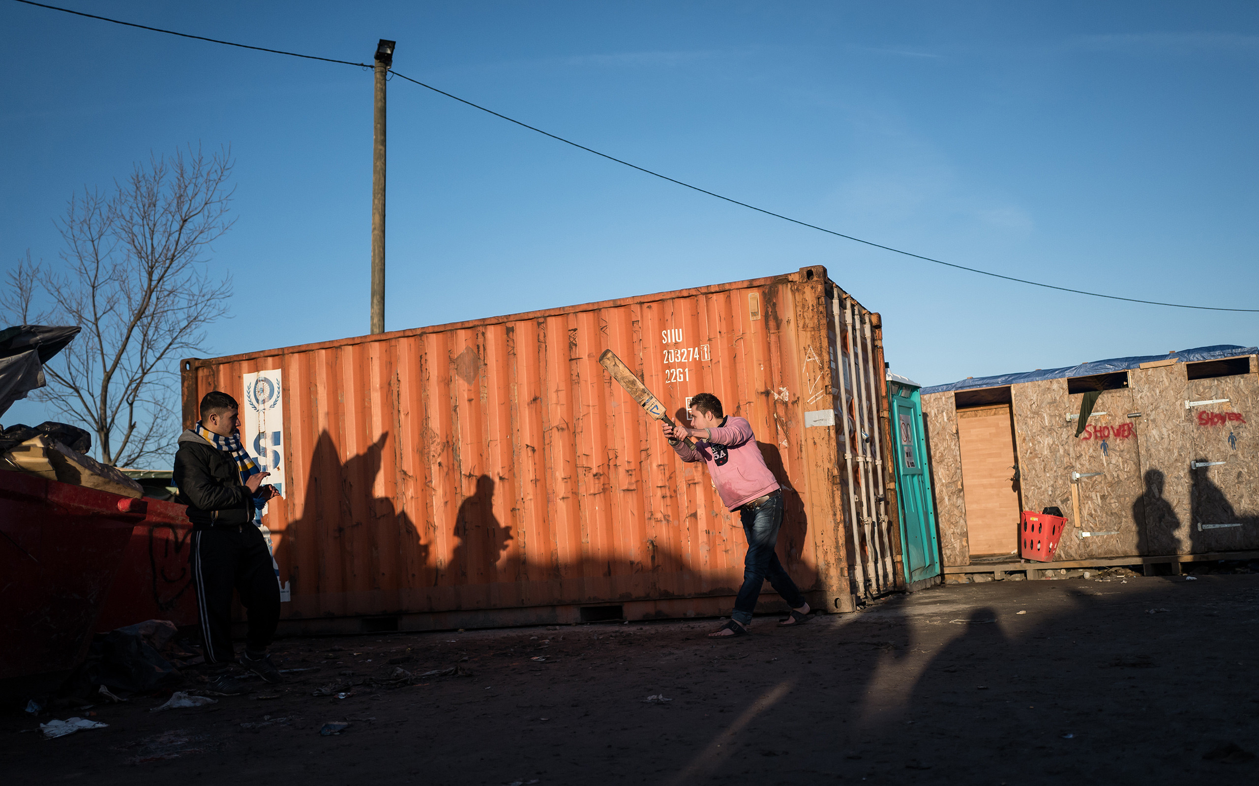 AFGHAN TEENAGERS PLAY CRICKET AGAINST A SHIPPING CONTAINER IN THE CALAIS 'JUNGLE', IN AN AREA OF THE CAMP KNOWN AS 'AFGHAN SQUARE'