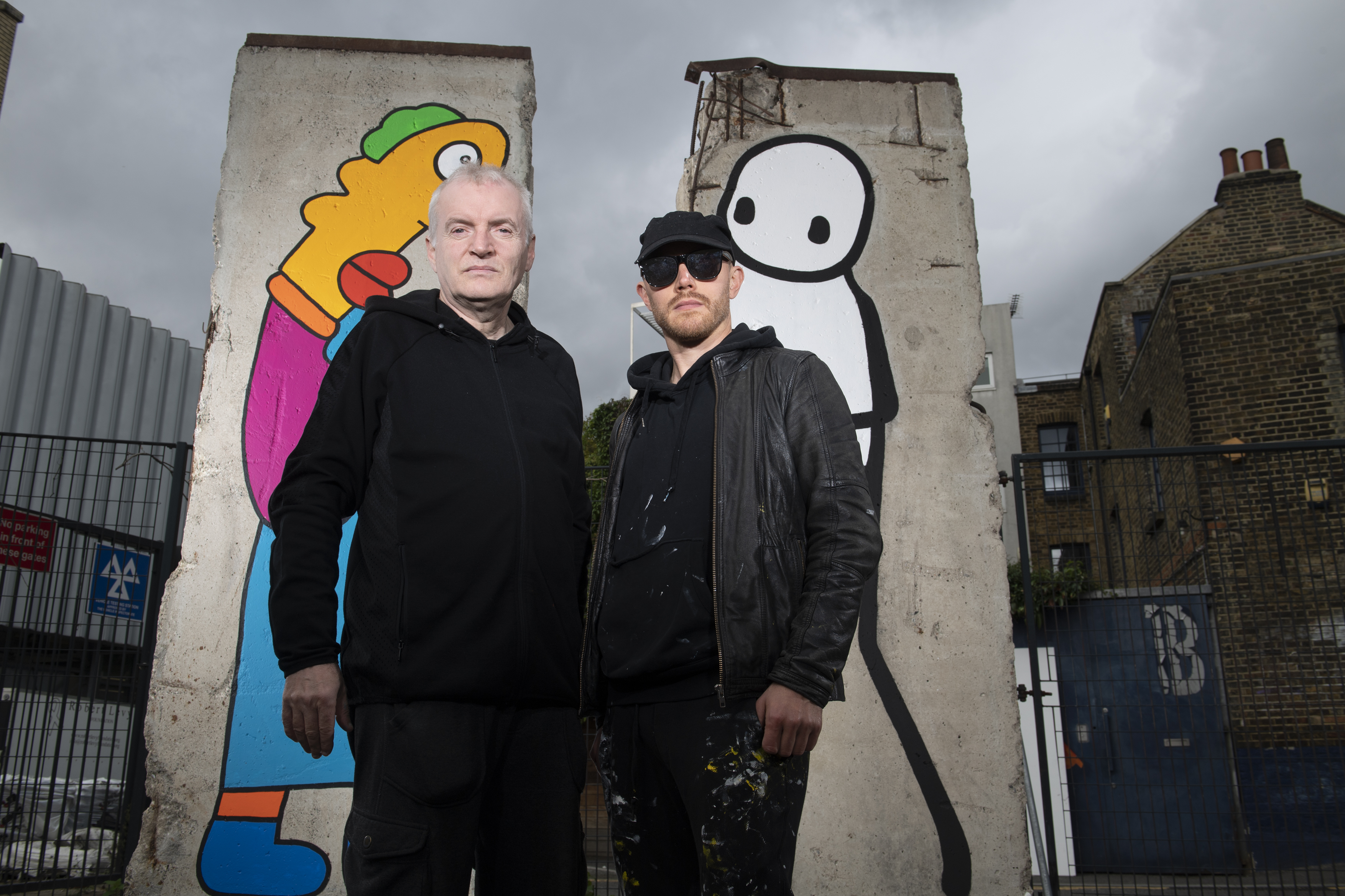 Thierry Noir and Stik stand in front of their work Wall