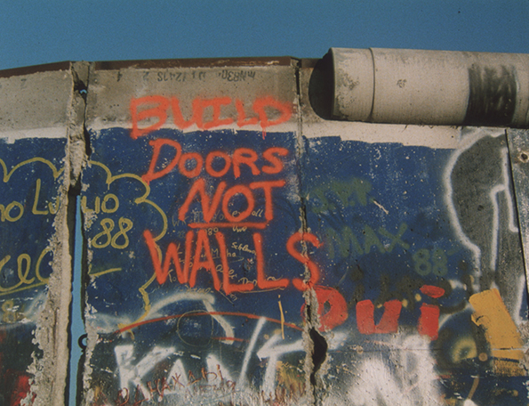 A man chips away at a part of the Berlin Wall. Grafffiti above him reads 'Build Doors Not Walls.' Still from the NATO film collection.