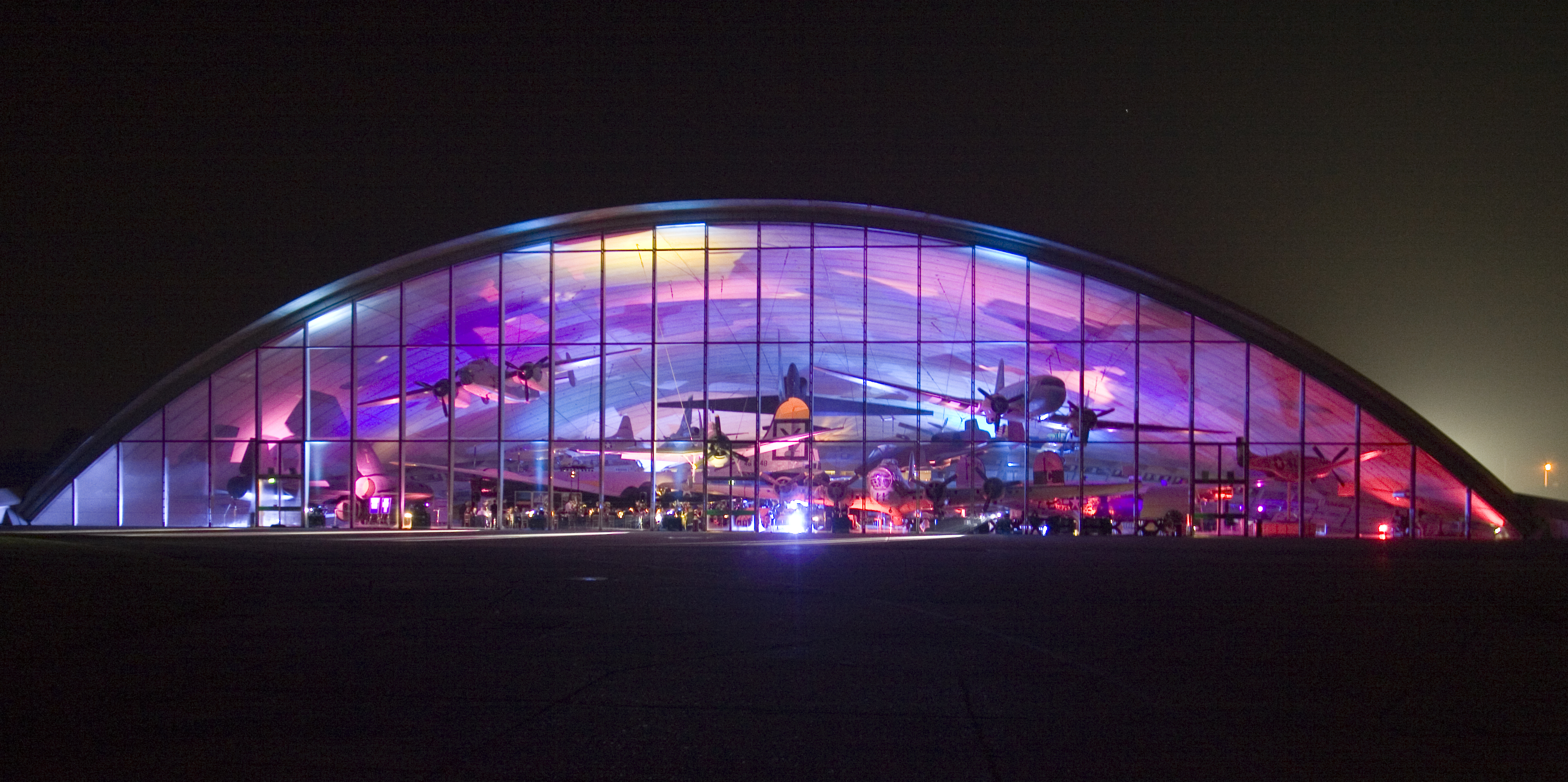 Exterior of Imperial War Museums Duxford hangar, lit in purple at night for an event