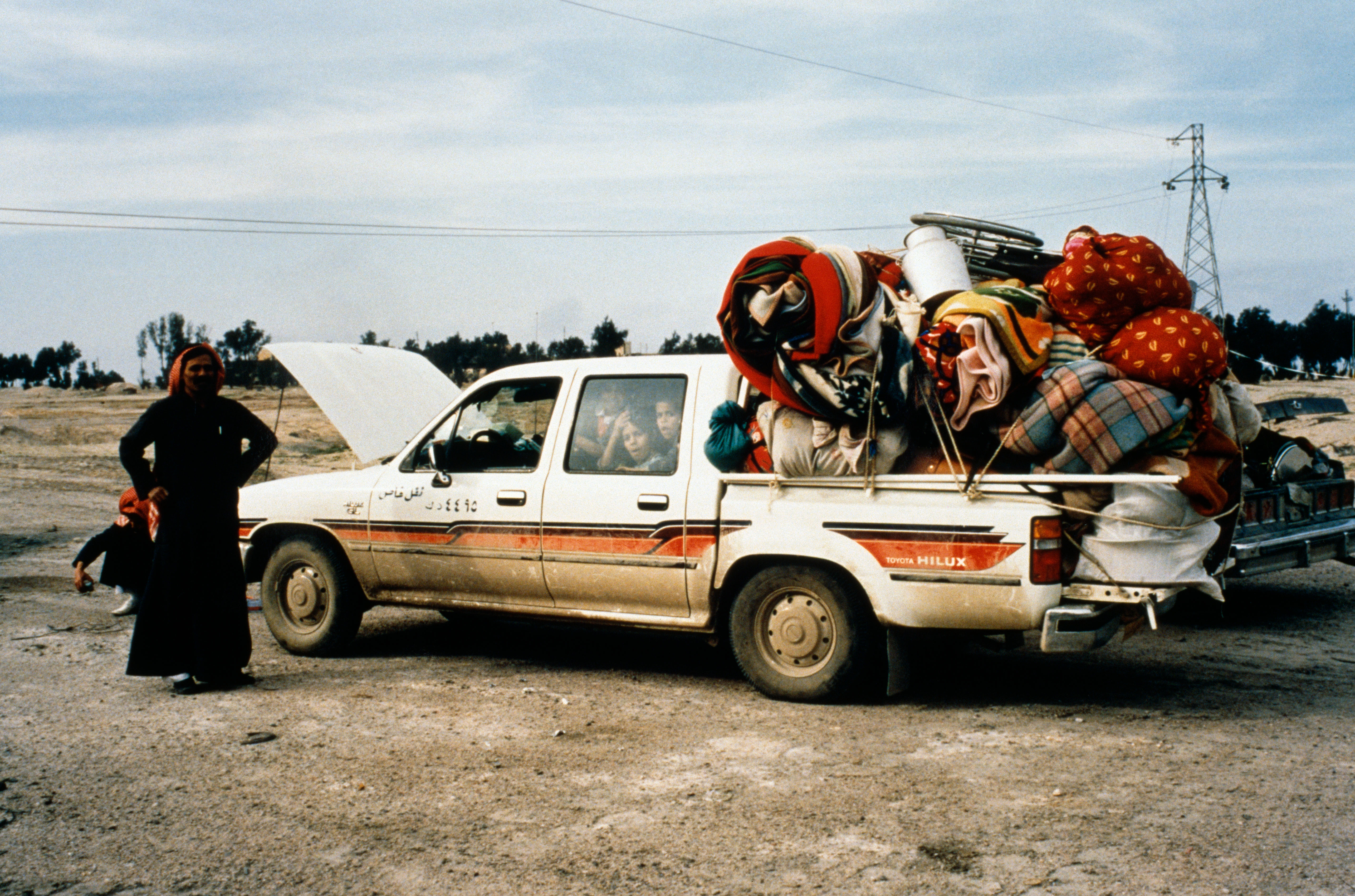 A family and their overloaded car at a refugee centre on the Iraq-Kuwait border, during the First Gulf War, 1991.