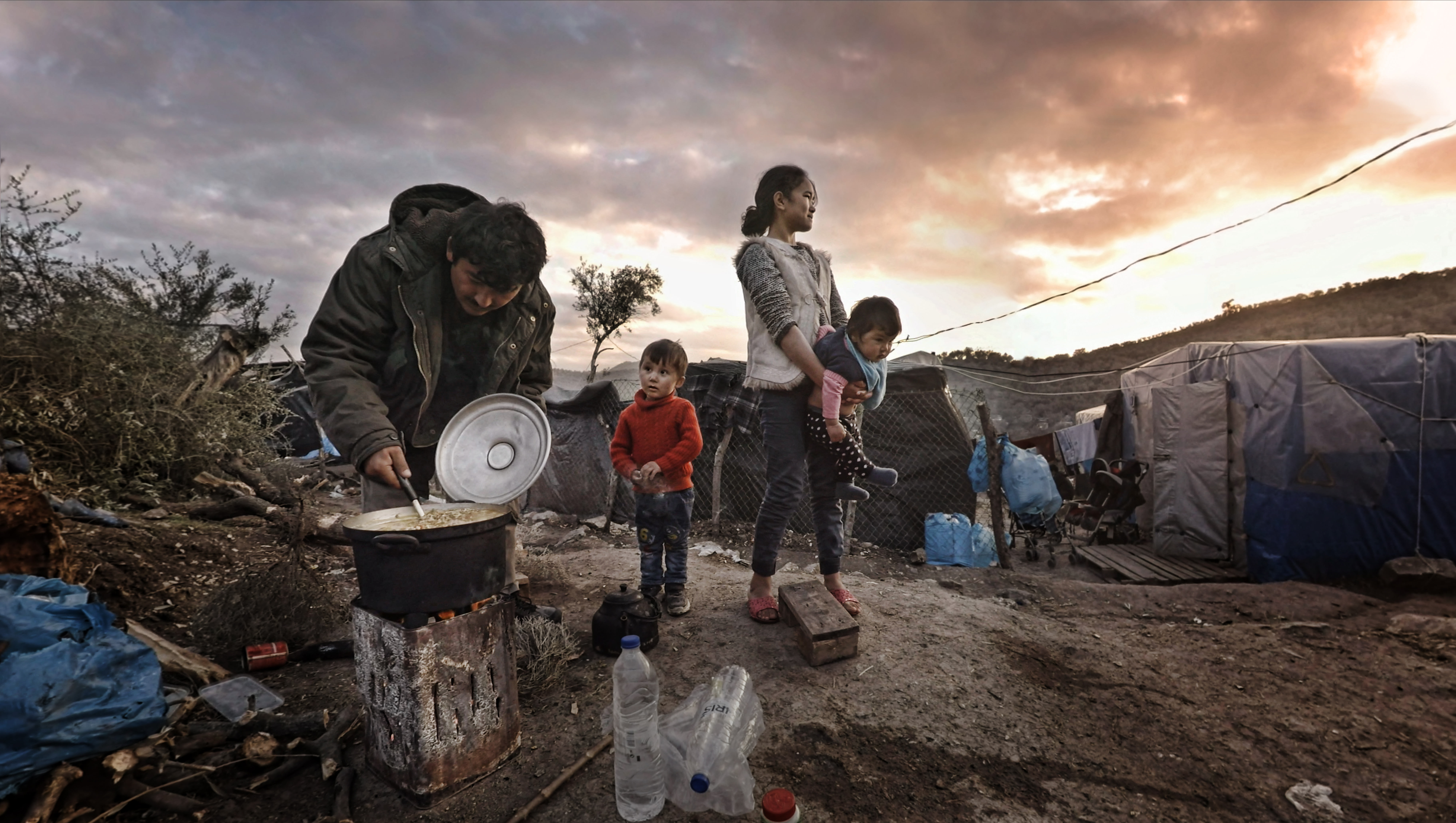 A family cooking on a makeshift cooker in a refugee camp.