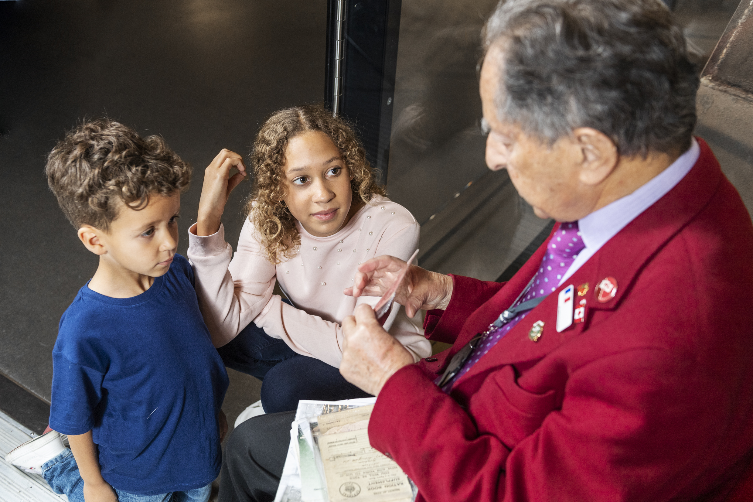 A volunteer talks to young visitors to Imperial War Museums
