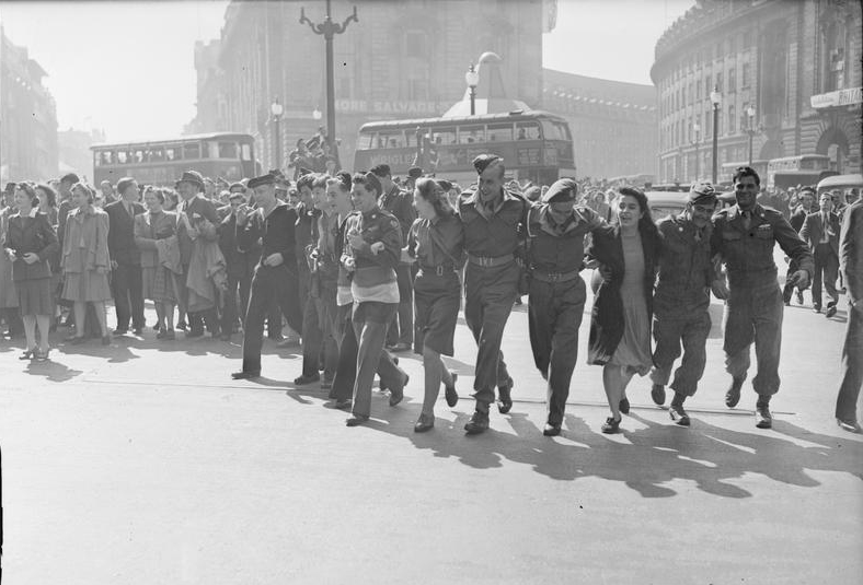 Civilians and service personnel in London's Picadilly Circus celebrate the news of Allied Victory over Japan in August 1945. © IWM D 25636