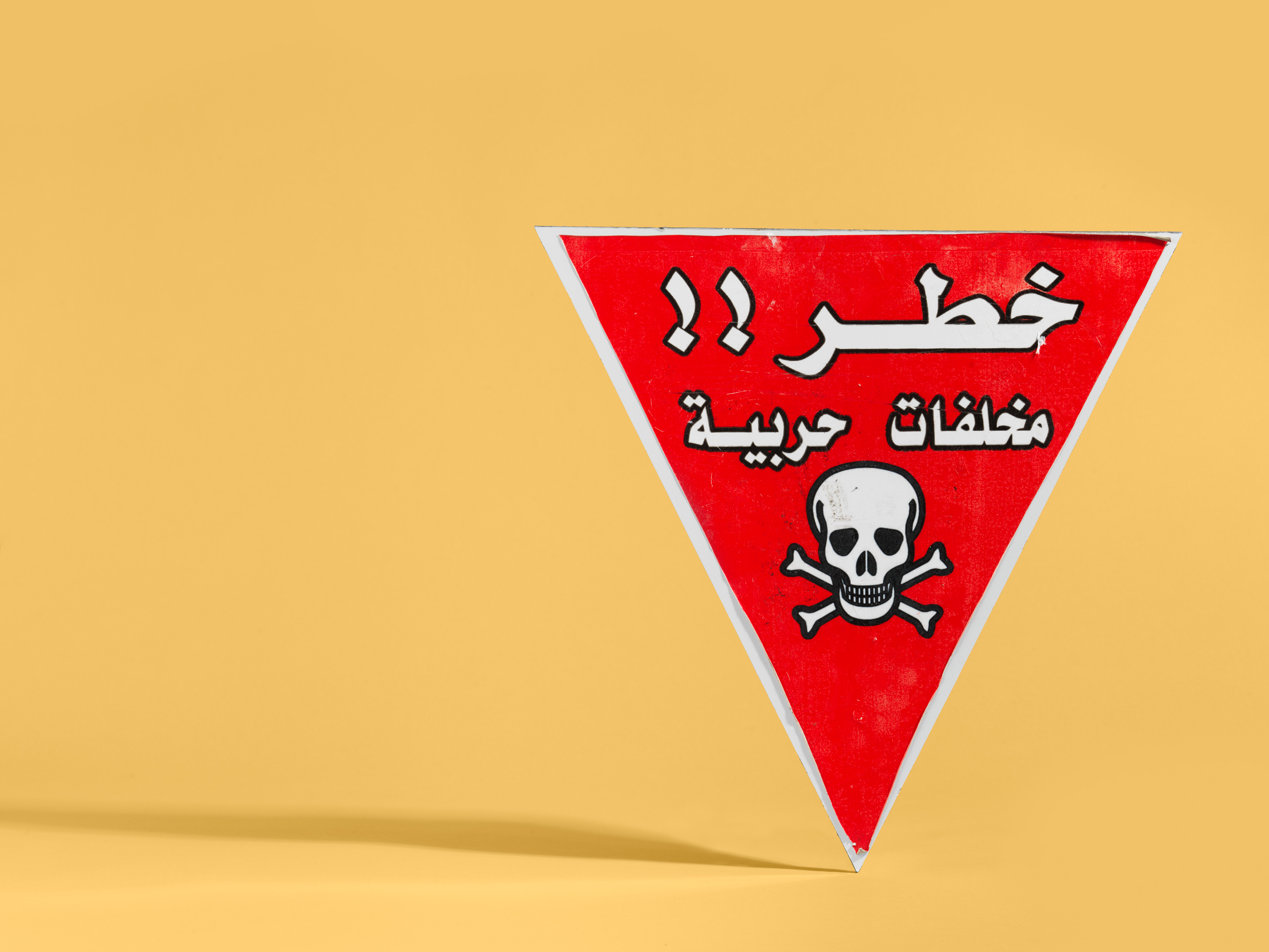 ICRC 'Explosive Remnants of War' warning sign from Iraq, 2019. In Iraq, ICRC employs local specialist staff to clear mines, bombs and other devices so that rebuilding work can begin and displaced people can return home.