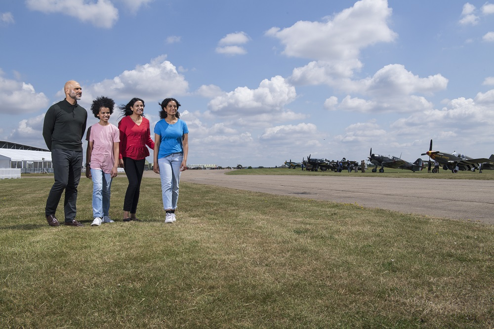 Family of 4 walking across IWM Duxford with line of aircraft behind