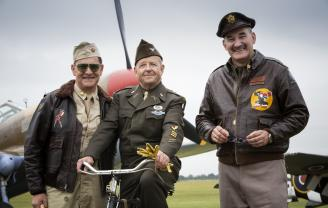 actors in ww2 dress in front of aircraft at Flying Legends