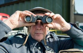 Man dressed in RAF 14 Group Royal Observer Corps dress holding binoculars and facing the camera