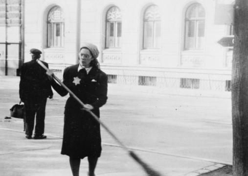 IWM HU 8967 A Jewish woman is forced to sweep the streets of Riga, Latvia, after its fall to the Germans, 22 August 1941. From late July, Jews in Latvia were ordered to wear a Star of David on their chest.