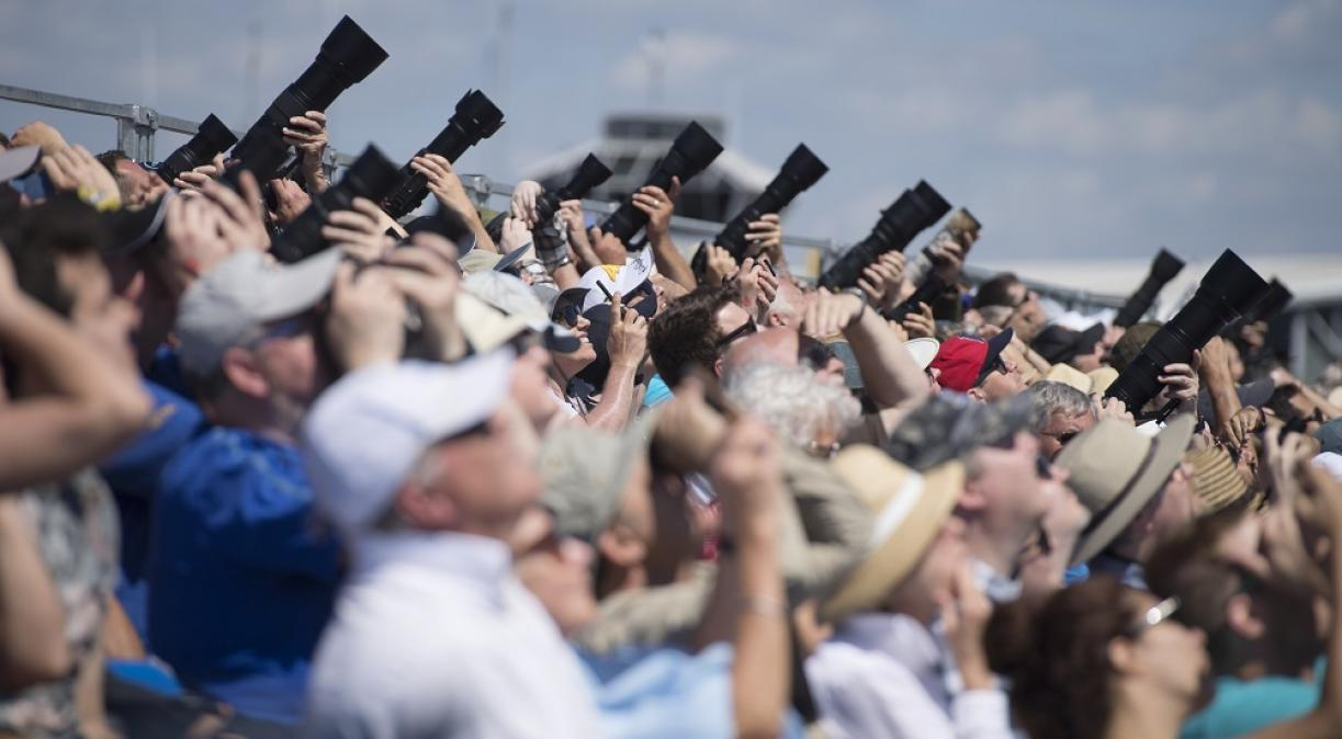 Grandstand visitors point their cameras to the sky at Duxford Air Shows
