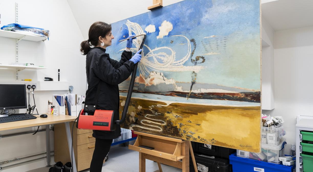 IWM's paintings conservator Nicoletta Tomassi conserving the painting BATTLE OF BRITAIN by Paul Nash, which will go on display in the Second World War Galleries