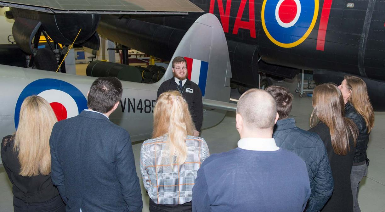 Members of the public enjoy a tour of IWM Duxford in front of a Lancaster Bomber