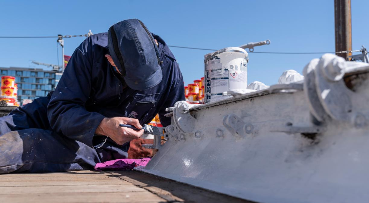 A member of IWM's Conservation team painting on HMS Belfast