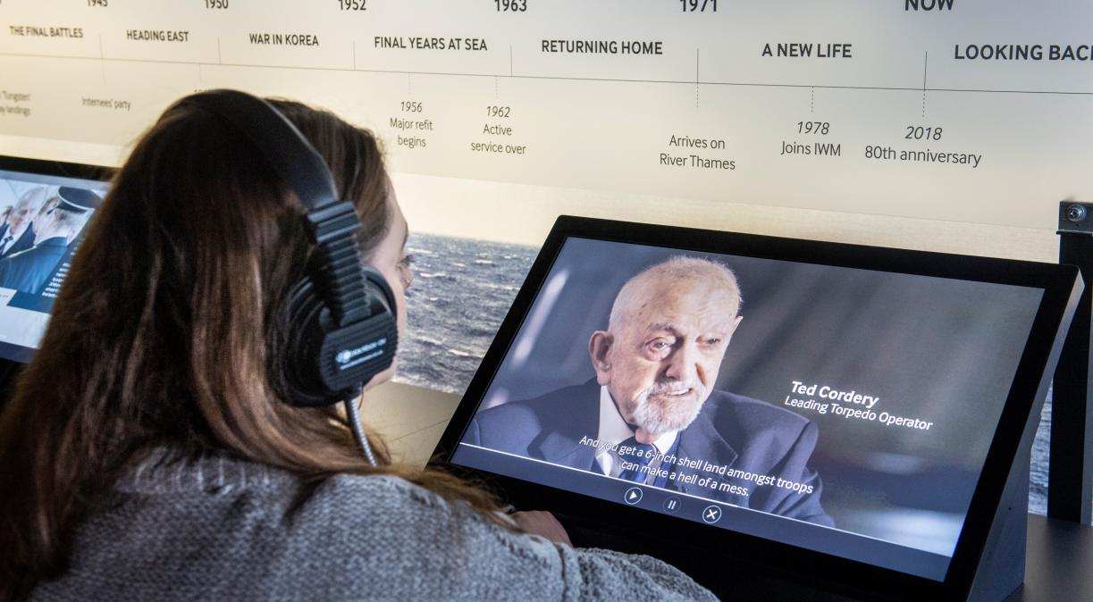 A visitor watching a film in the 'Serving the Seas' exhibition on board HMS Belfast