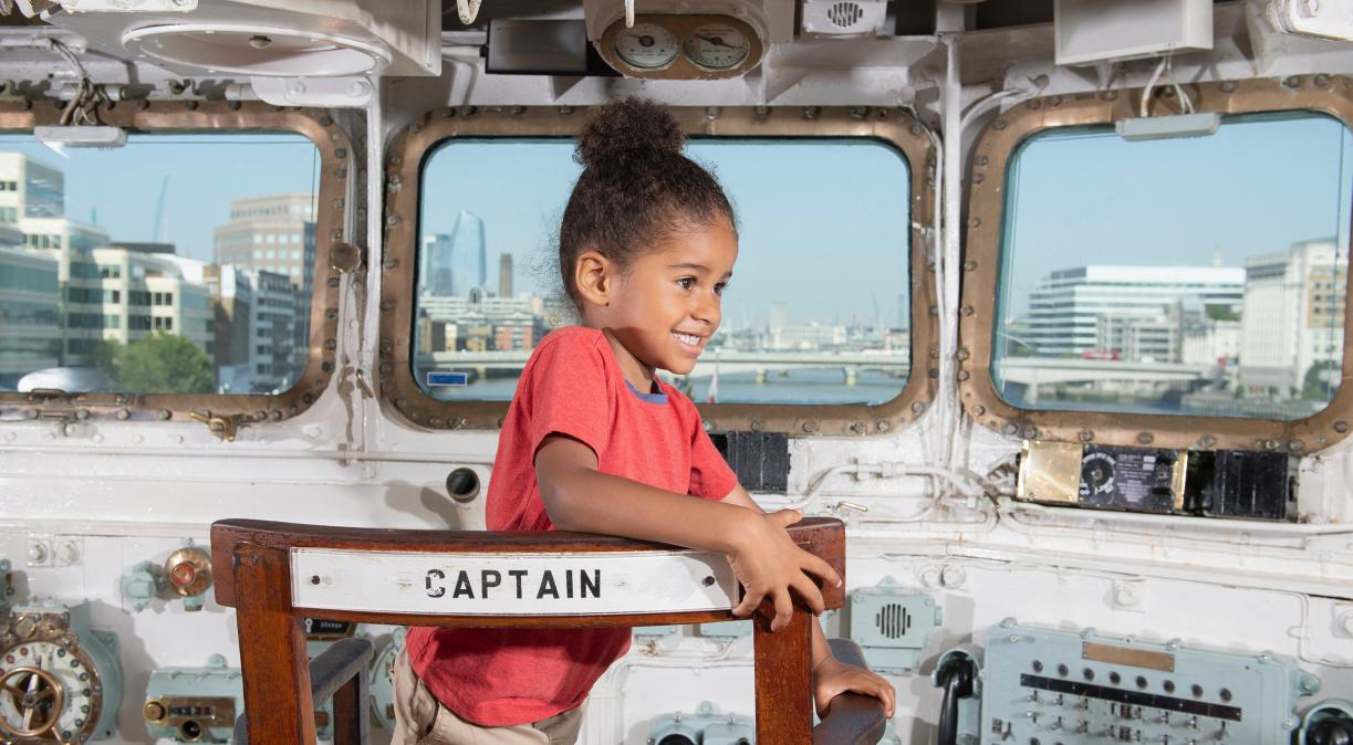 A visitor sitting in the Captain's chair on board HMS Belfast