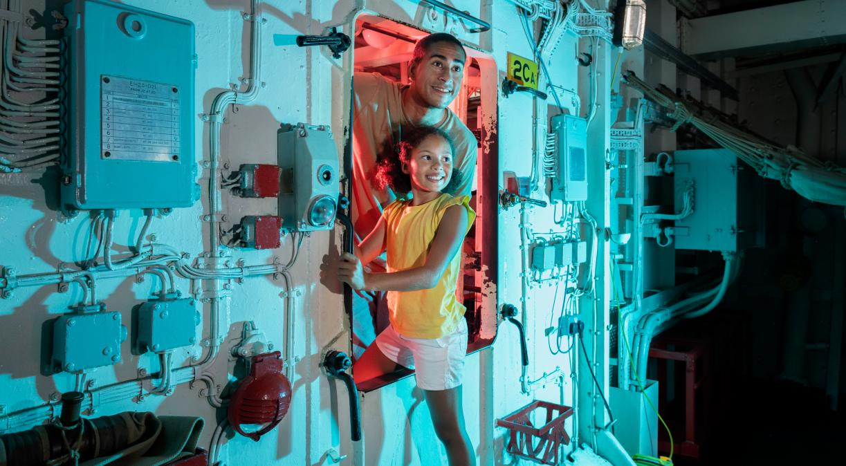 Visitors ducking through a hatch into the Arctic Messdeck on board HMS Belfast