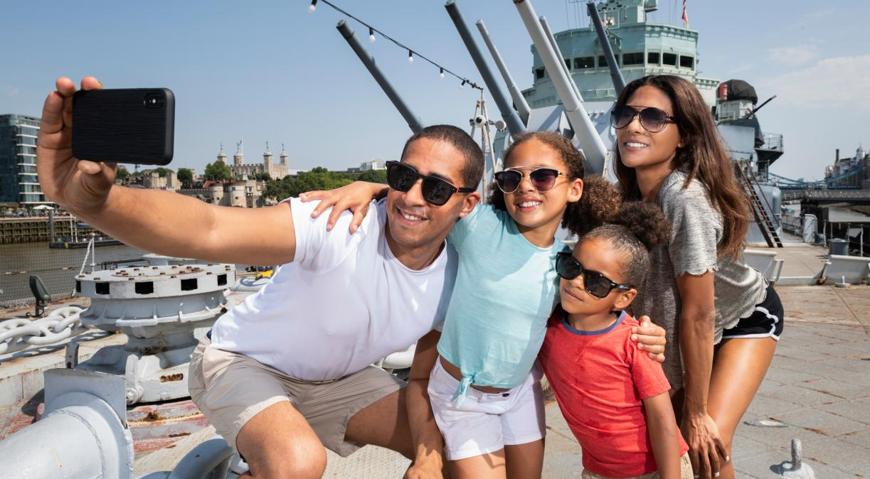 A family taking a photo on the Fo'c'sle on board HMS Belfast