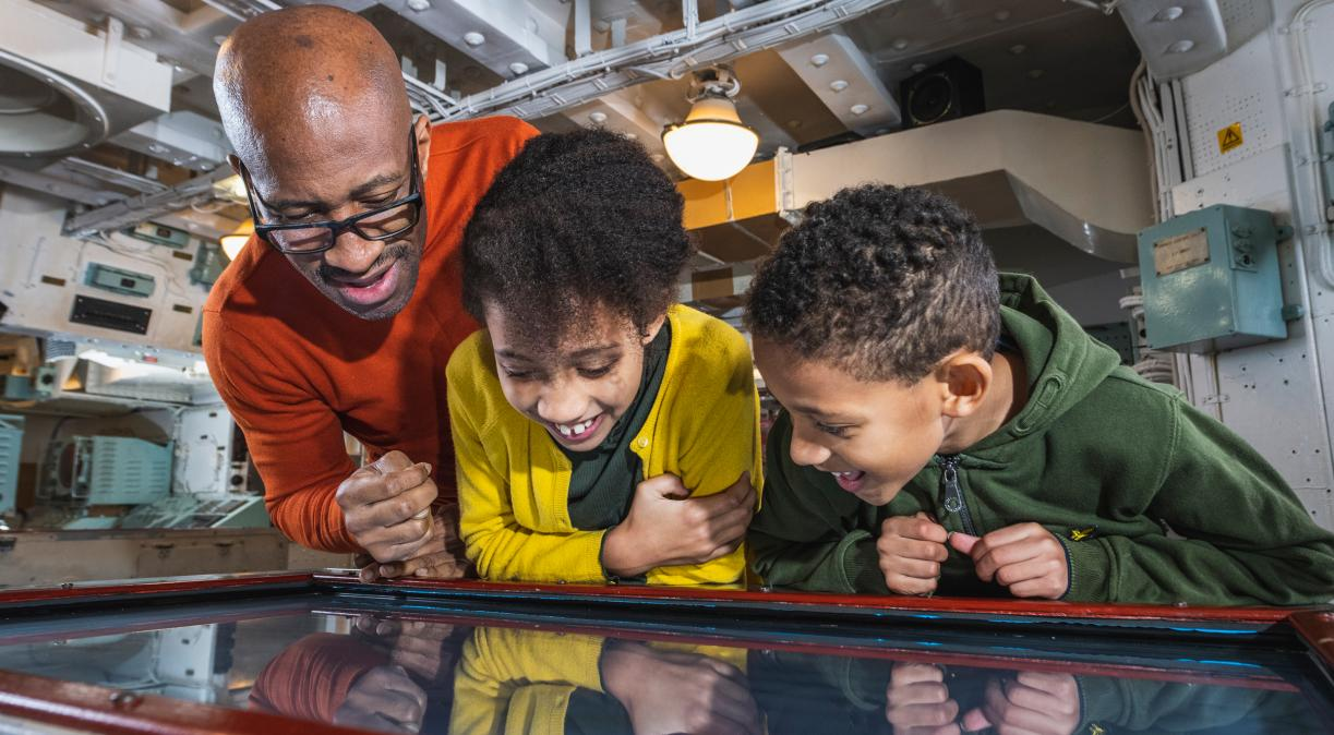A family using the interactive plotting table in the Operations Room on board HMS Belfast