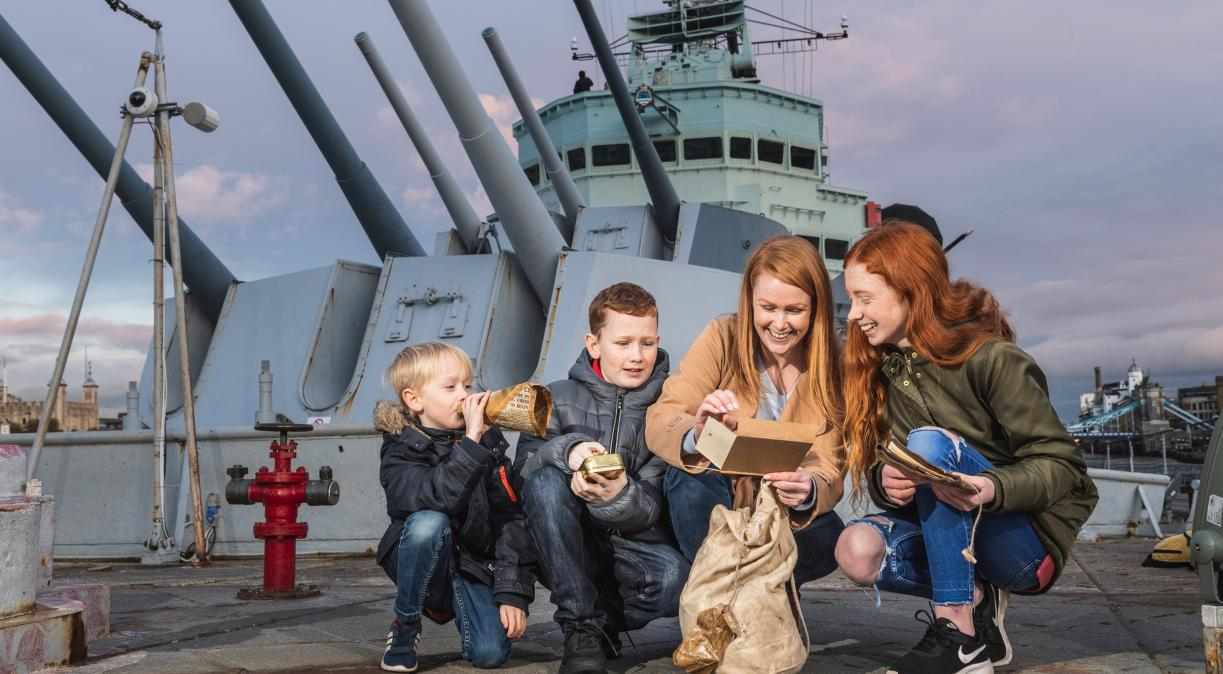 A family taking part in the family activity 'Family Mission: D-Day Edition' on board HMS Belfast