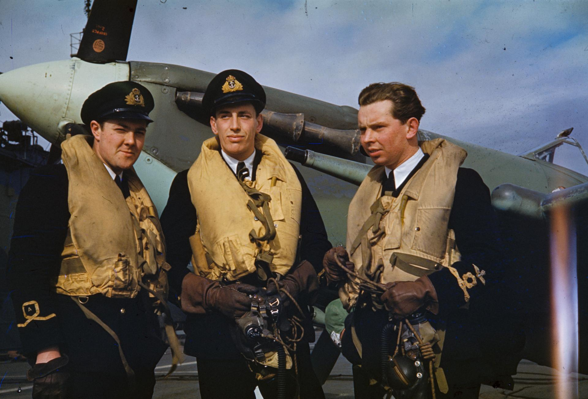 Three Fleet Air Arm pilots wearing 'Mae West' life-jackets wait for the order of the day on board an aircraft carrier. A Supermarine Seafire can be seen in the background.