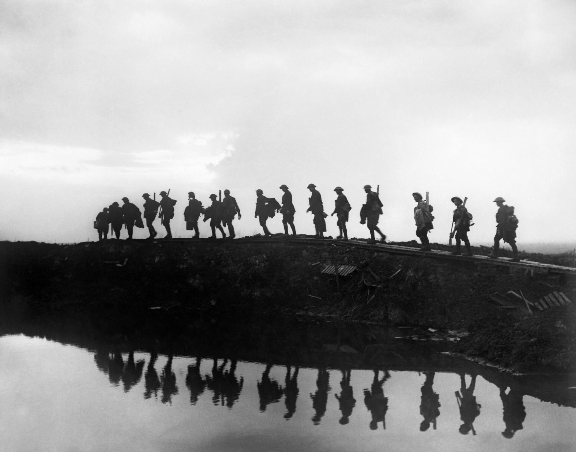 A line of troops seen in silhouette passing along a small ridge alongside water on their way to relieve the front line near Hooge.