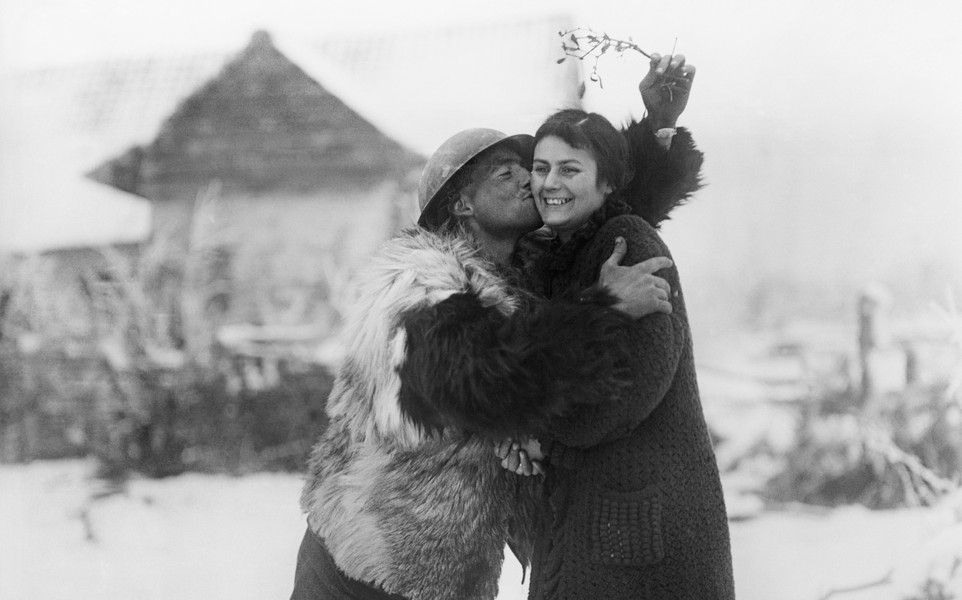 © IWM (Q 8354) A soldier of the Machine Gun Corps in a sheepskin coat kissing a French farm-girl under a sprig of mistletoe, near Hesdin, 20 December 1917.