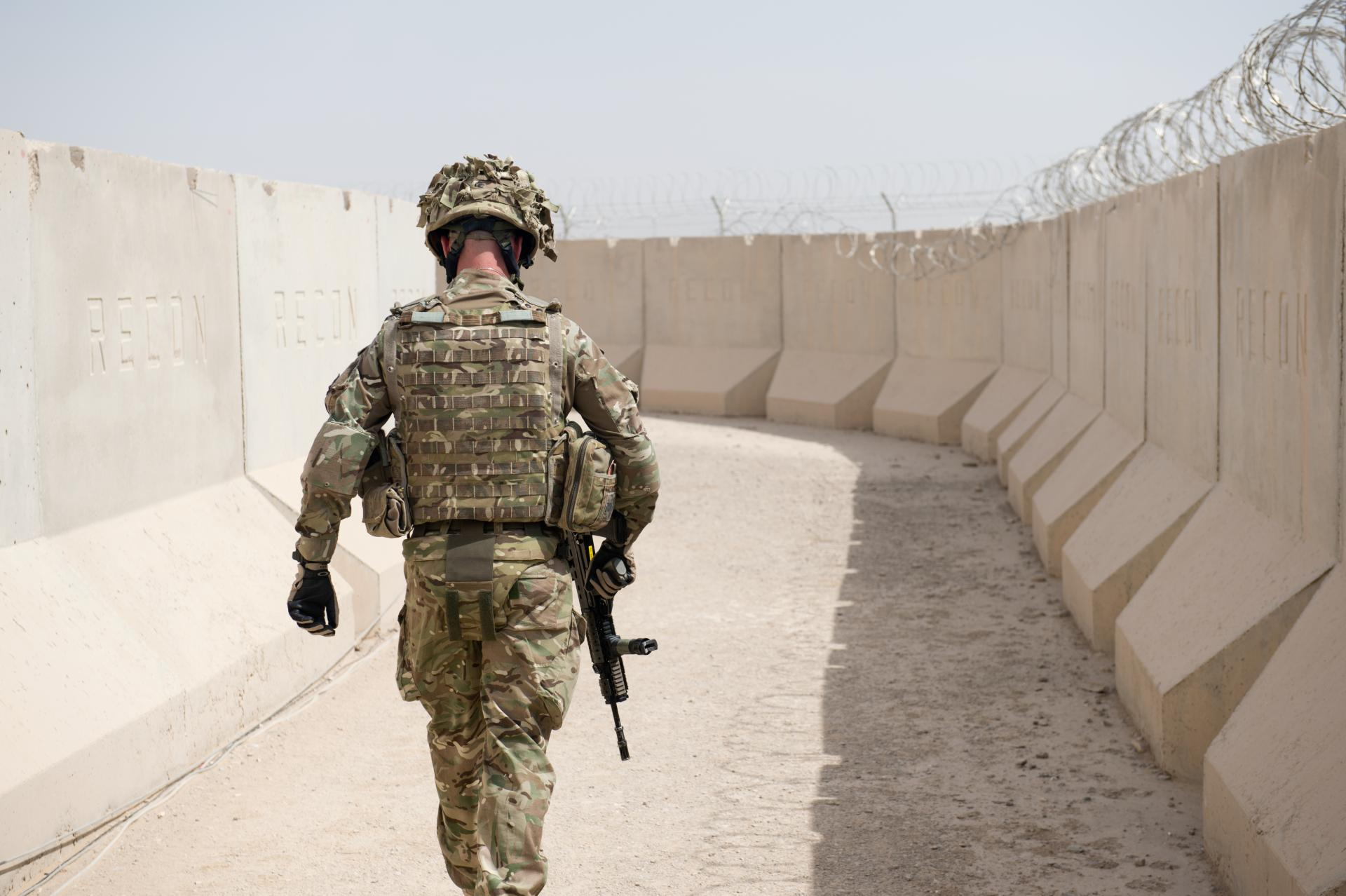 A soldier in uniform walks away from the camera at Camp Bastion, the principal British base in Helmand Province, Afghanistan