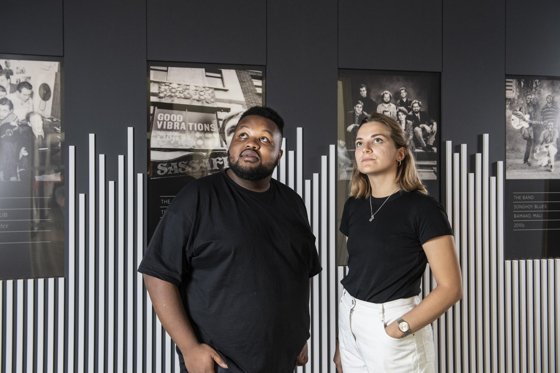 Young man and woman stand in front of black and white images of Rebel Sounds exhibition