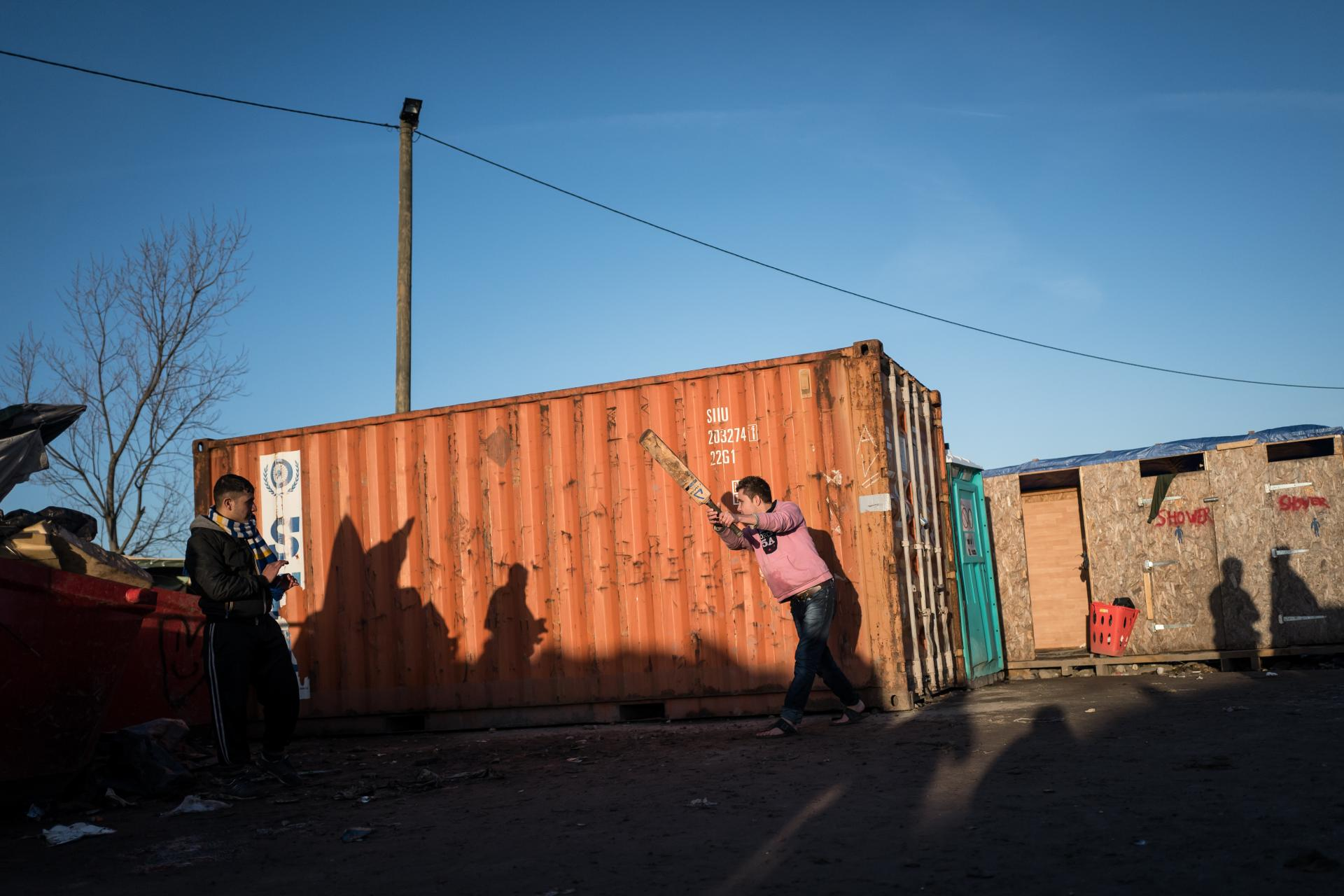 Afghan teenagers play cricket against a shipping container in the Calais 'Jungle', in an area of the camp known as 'Afghan Square'.