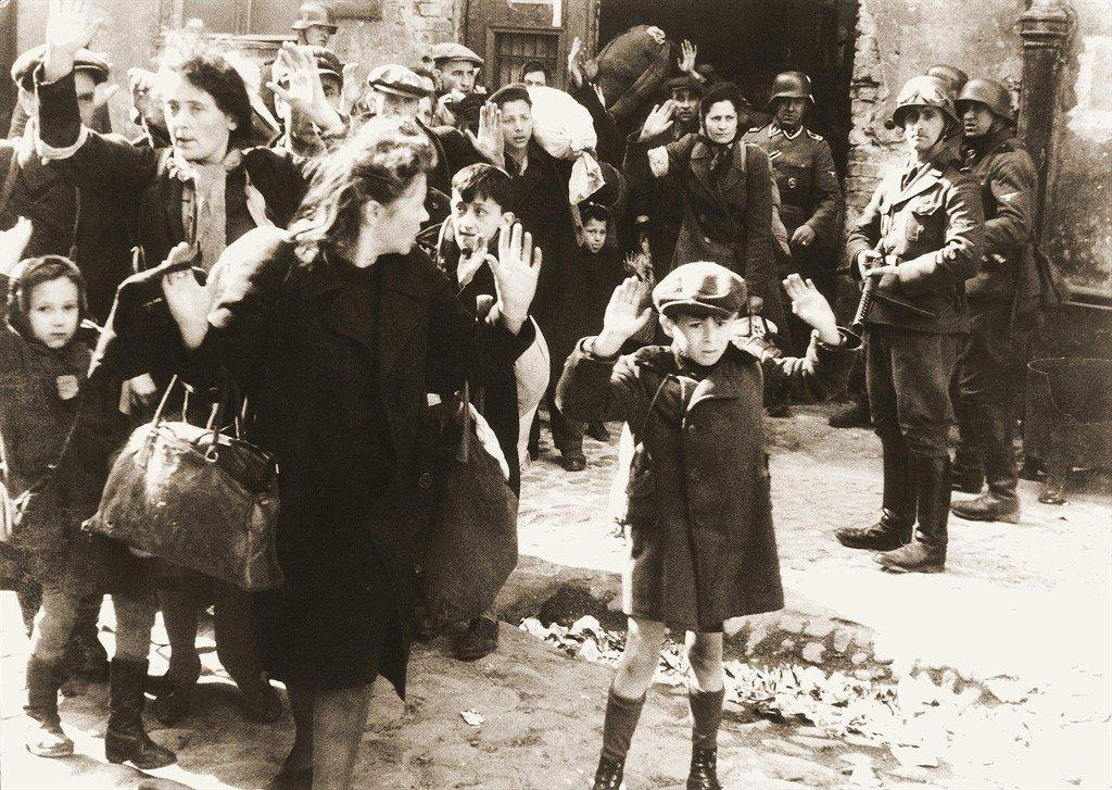 This photo shows Jews held at gunpoint by German soldiers during the suppression of the Warsaw Ghetto Uprising in May 1943.