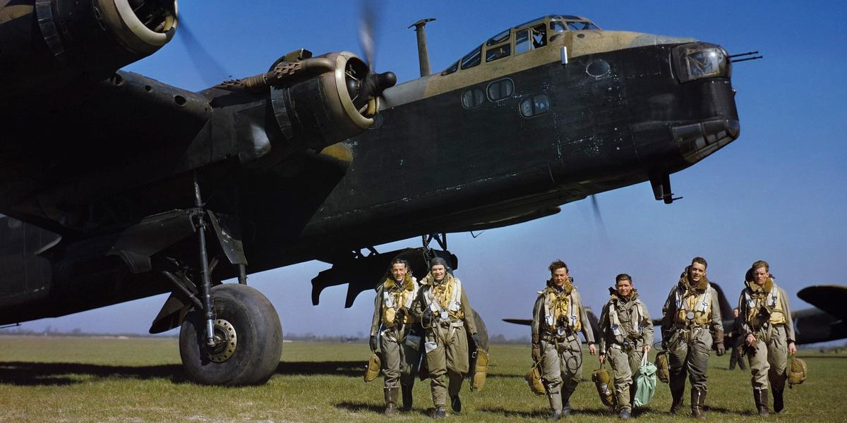 Aircrew in full flying kit walking beneath the nose of Short Stirling Mark I, N3676 'S', of 1651 Heavy Conversion Unit at Waterbeach, Cambridgeshire while the ground crew run up the engines.