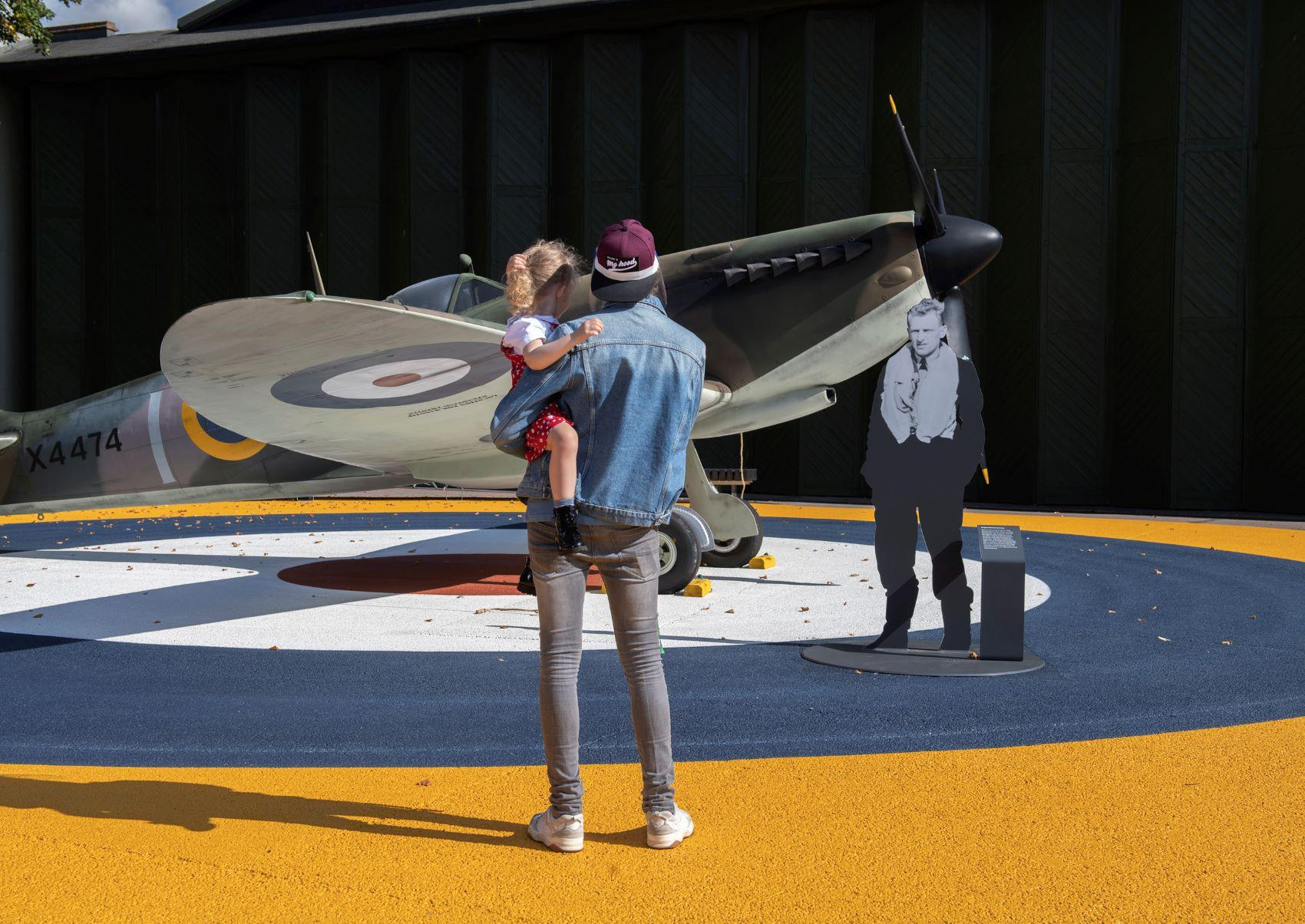 Visitors stand next to a Spitfire display at IWM Duxford