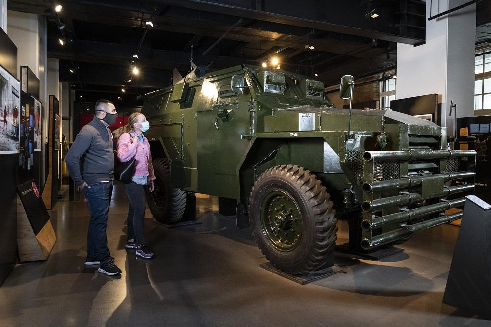 Visitors walking past an armoured car in IWM London
