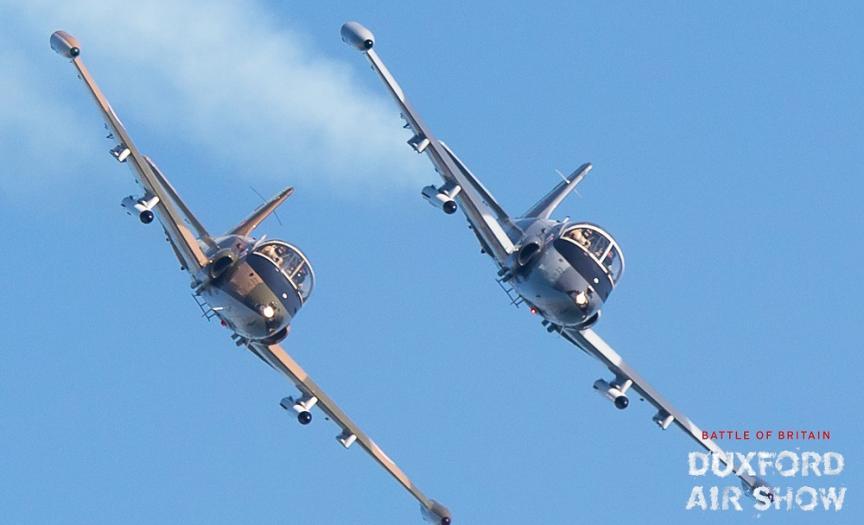 Strikemaster pair with smoke against a blue sky