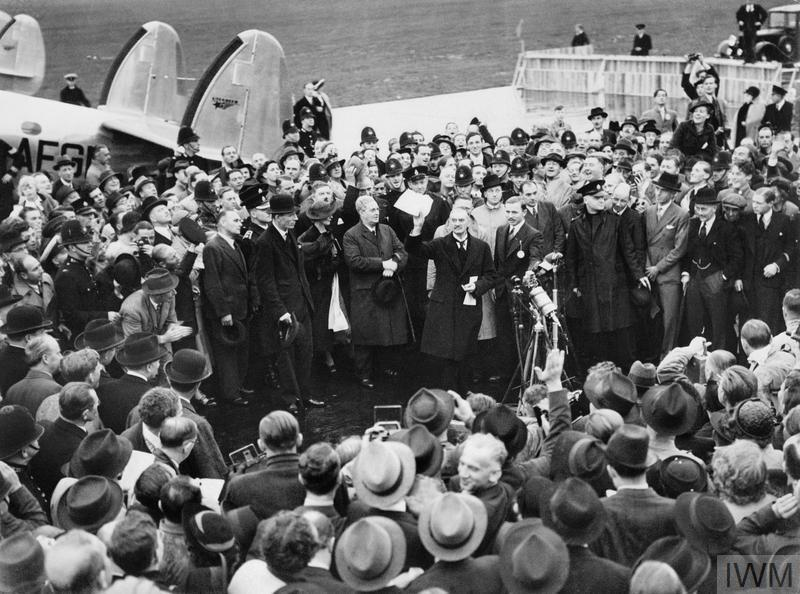 "Neville Chamberlain, the Prime Minister, makes a brief speech announcing """"Peace in our Time"""" on his arrival at Heston Airport after his meeting with Hitler at Munich, 30 September 1938."