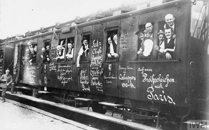 "Cheerful troops of the German Landsturm (still in civilian cloths) departing for a training camp in a train covered with slogans i.e. ""Auf zum Preisschiessen nach Paris - Sent on the Price Shooting to Paris"""
