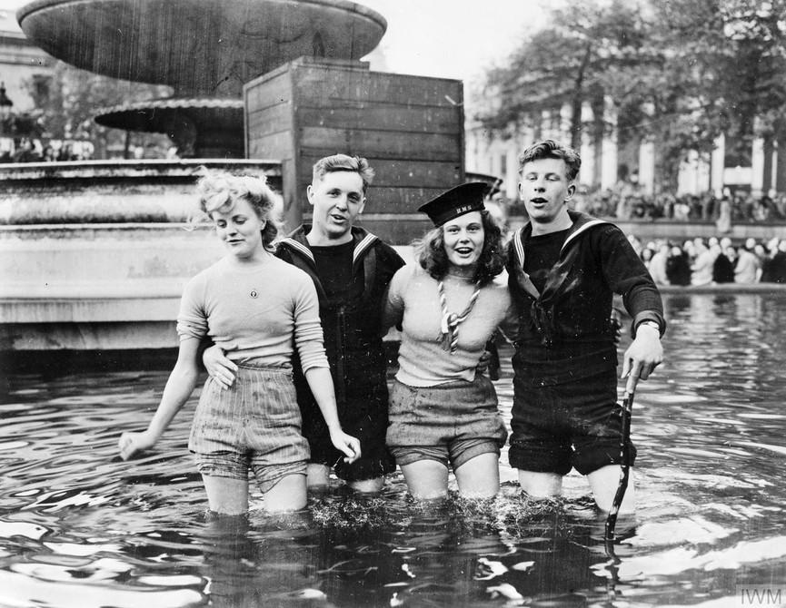 Two British sailors and their girlfriends wading in the fountains in Trafalgar Square on VE Day.