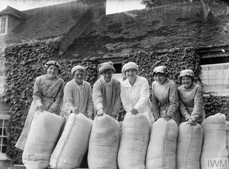 A group of smiling female workers pose with sacks of flour in the grounds of a British mill during the First World War.